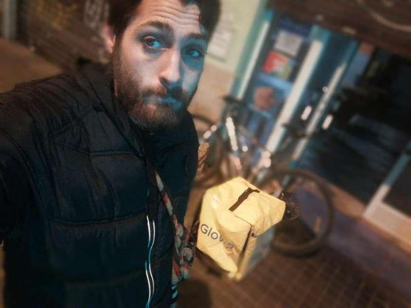 Pepe Forés, repartidor de UberEats, que todavía utiliza una bolsa de la plataforma donde trabajaba antes, Glovo, durante una jornada de trabajo. EFE/EFE
