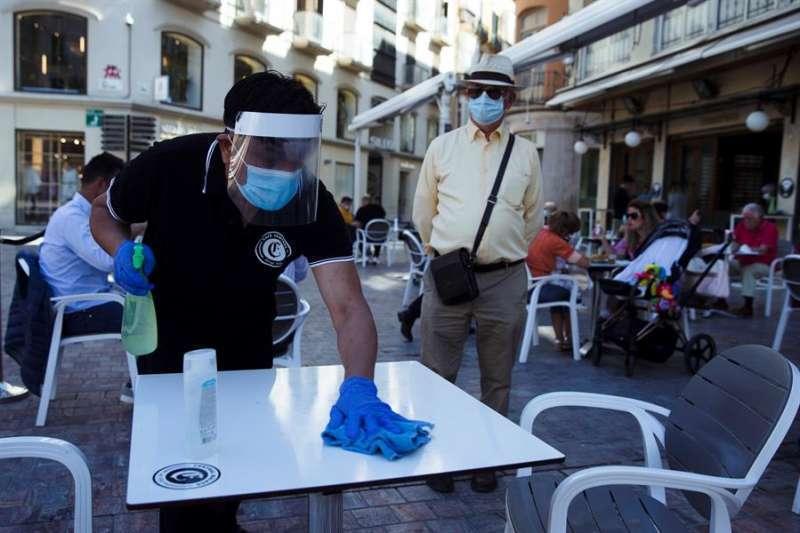 Un camarero limpiando una mesa con protección anticoronavirus