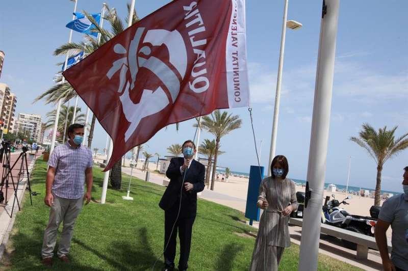 El president de la Generalitat, Ximo Puig, y la alcaldesa de Gandía, Diana Morant, izan la bandera Qualitur en la playa de Gandía. EFE