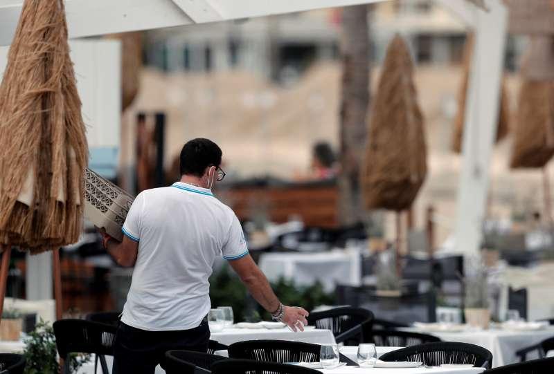 Un camarero monta las mesas en una terraza de un negocio de la Comunitat Valenciana. EPDA