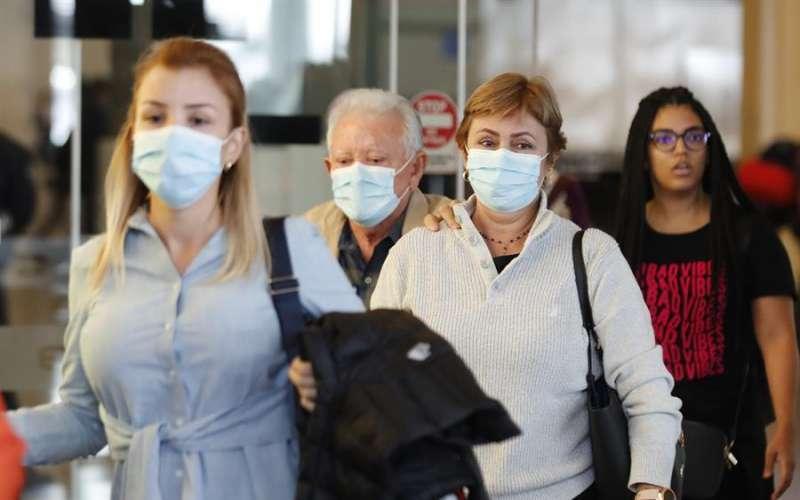 Varias personas caminan con mascarrilla. EFE
