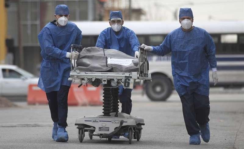 Trabajadores sanitarios conducen una camilla con el cuerpo de una persona fallecida por la covid-19. EFE/Archivo