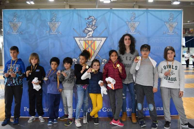 Espadistas con sus medallas junto a su entrenadora.