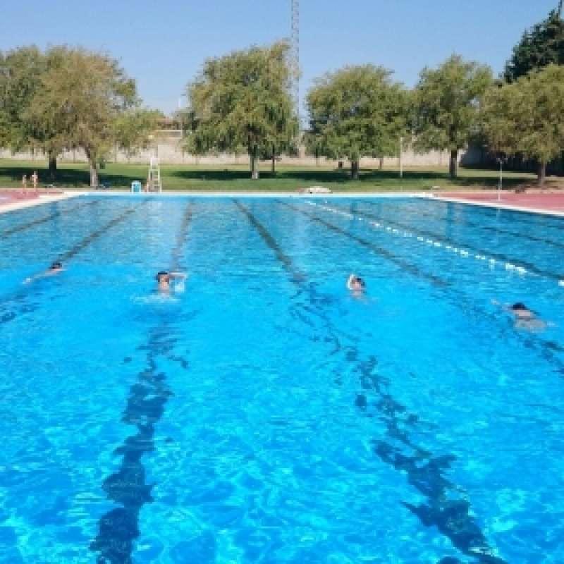 Unos niños nadan en una piscina.