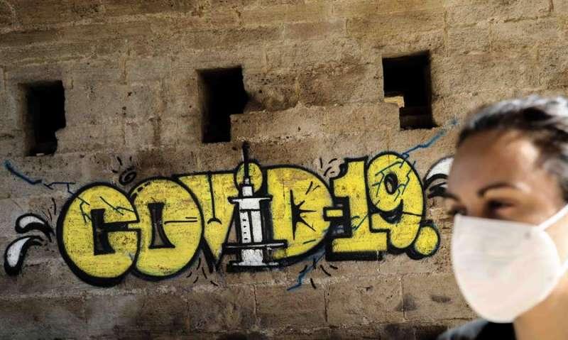 Una persona con mascarilla pasa ante un grafiti en Valencia. EFE