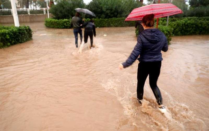 Varias personas cruzan una calle inundada por la lluvia. EFE/Kai Försterling/Archivo
