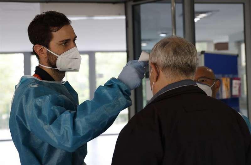 Personal sanitario del SERMAS toma la temperatura a una persona. EFE/Zipi/Archivo
