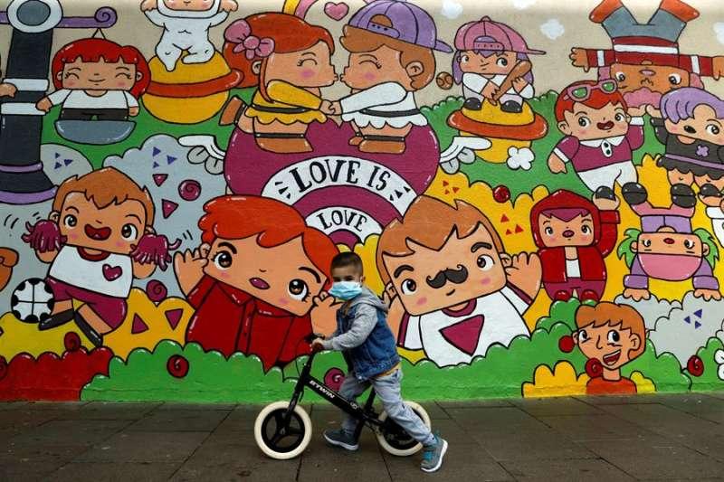 Un niño con mascarilla juega con su bicicleta. EFE/Archivo