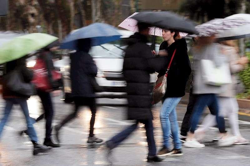 Varias personas se protegen de la lluvia caída esta mañana con paraguas. EFE
