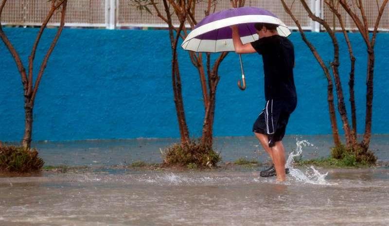 Una persona vadea una calle este viernes cuando las provincias de Castellón y Valencia están en alerta naranja por precipitaciones de intensidad muy fuerte y con tormenta. EFE/Kai Försterling