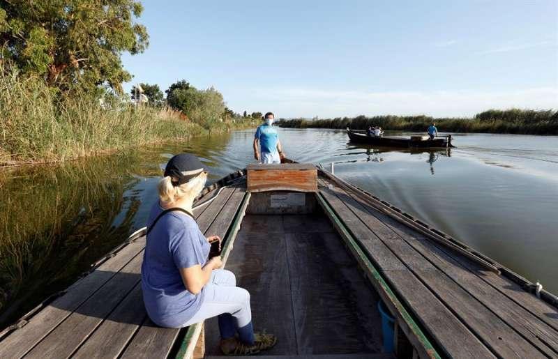 Una turista de paseo en un barca por La Albufera. / EFE