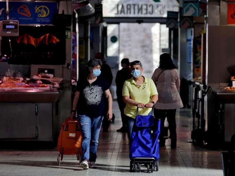 Dos mujeres de compra con mascarillas