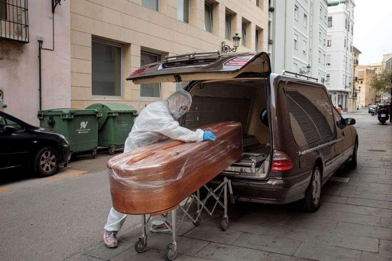 En la imagen, un operario de funeraria introduce el féretro de un fallecido por covid en el vehículo. EFE