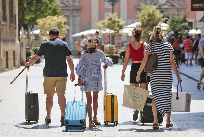 Una familia carga con sus maletas en pleno centro de València. EFE/Manuel Bruque/Archivo