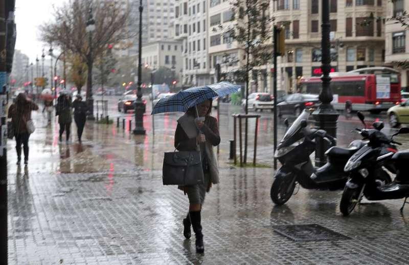 Una mujer se protege de la lluvia en el centro de Valencia. EFE/Archivo