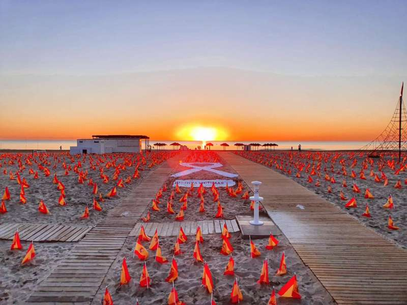 Imagen de ANVAC del amanecer en la playa de la Patacona con las miles de banderas de España.