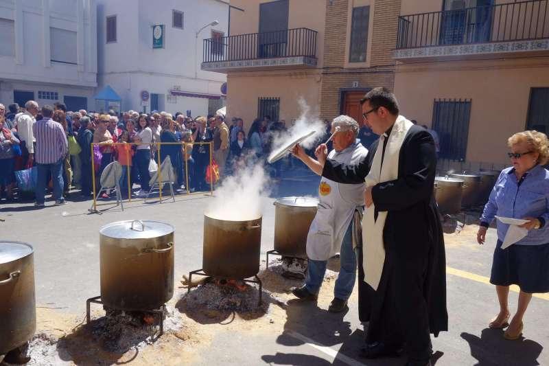 El párroco bendiciendo las ollas. EPDA
