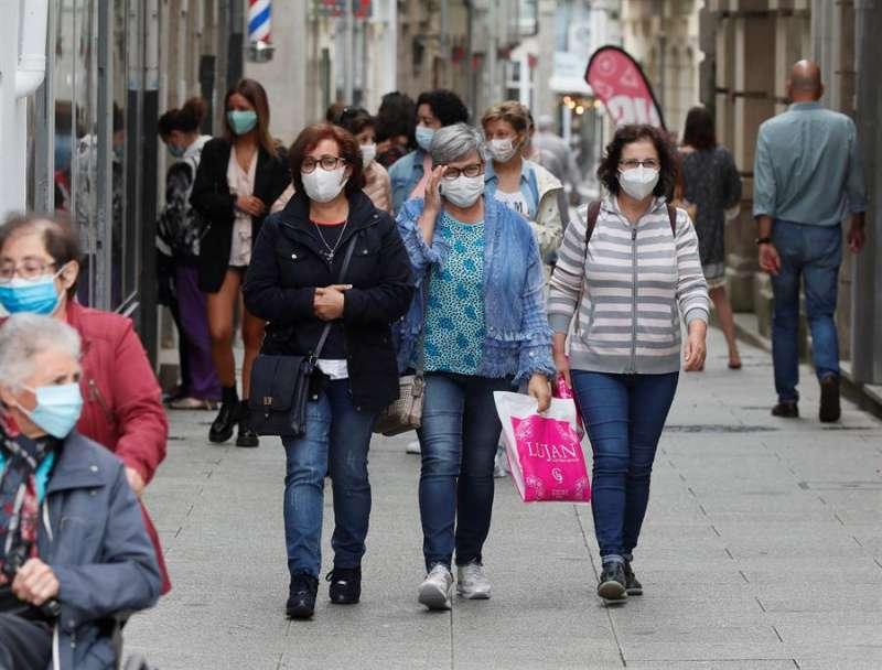 Varias personas caminan con mascarilla por un centro comercial. EFE