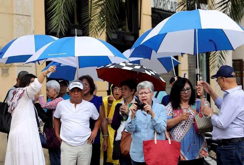 Unos turistas, protegidos con paraguas, recorren el centro de la ciudad de València. EFE