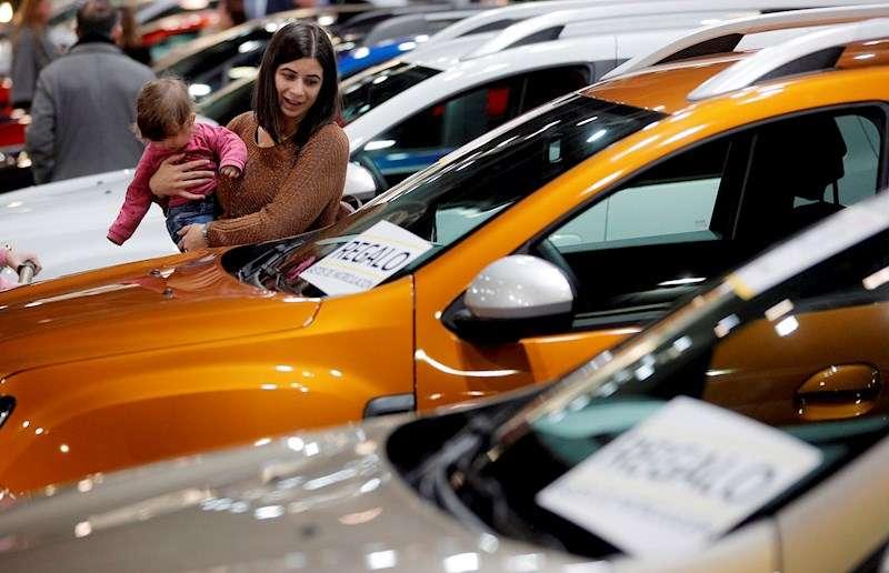 Una mujer contempla un vehículo en una feria del automóvil de València. EFE