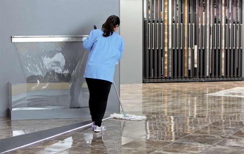 Una mujer de la limpieza repasa el suelo de un expositor en una feria de la cerámica. EFE/Manuel Bruque/Archivo