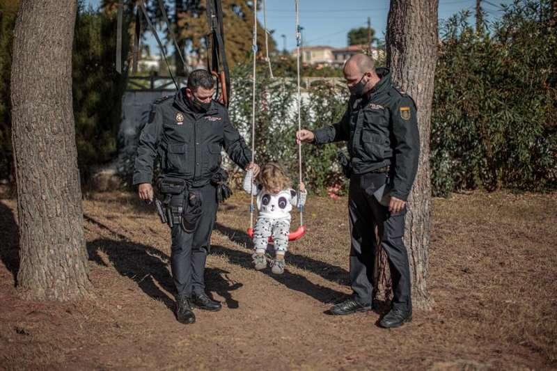 Los dos agentes de la Policía Nacional juegan con Marina, la niña de dos años a la que salvaron la vida. EFE