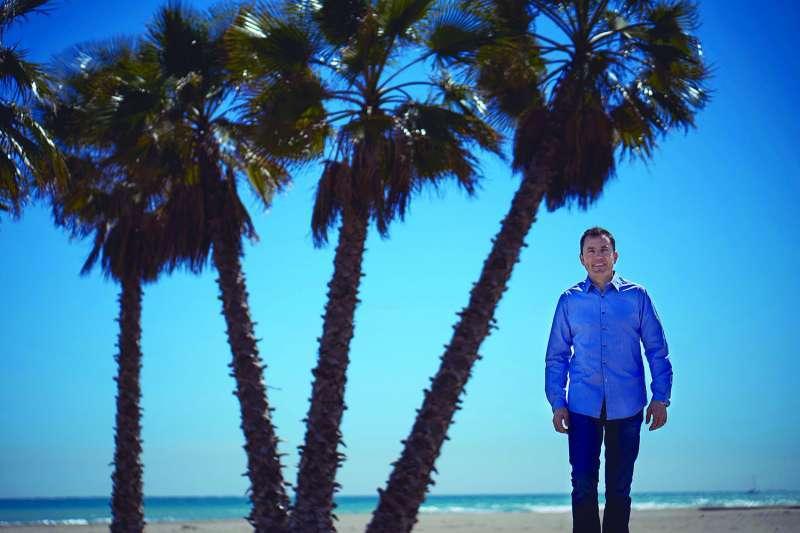 El alcalde de Canet, en la playa junto a las palmeras plantadas en la anterior legislatura. EPDA