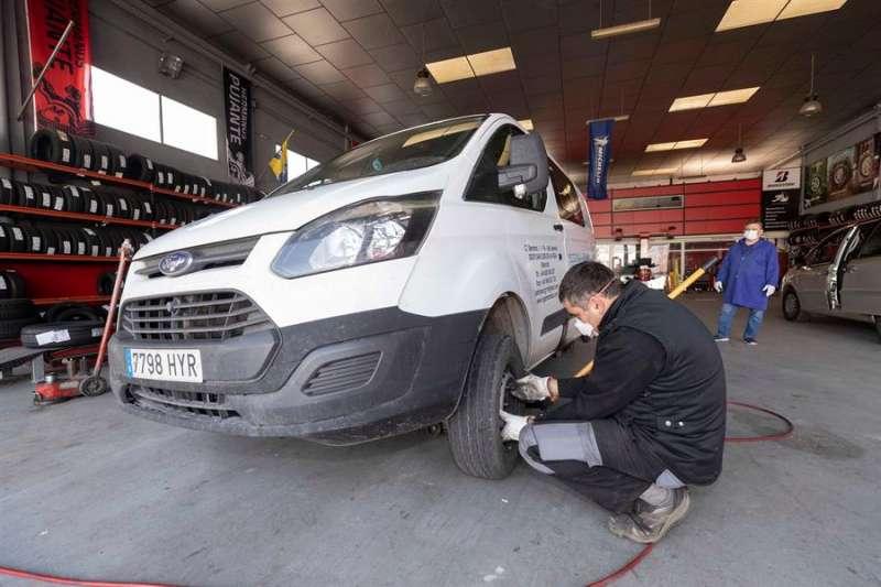 Un trabajador de una empresa de neumáticos cambia una rueda a una furgoneta de reparto, una labor considerada como esencial por el decreto del gobierno para hacer frente a la pandemía del COVID 19. EFE/Marcial Guillén/Archivo